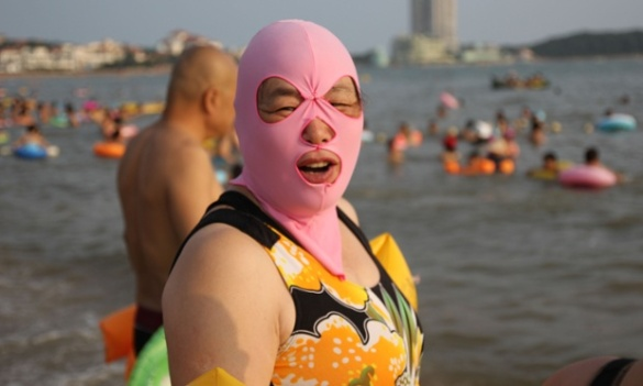 Women balaclava style face masks at a beach, Qingdao, Shandong Province, China - 14 Aug 2014